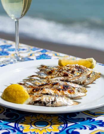 Sardinen Espeto, Fisch auf Stiel-Barbecue nach Malaga-Art, zubereitet auf Brennholz von Olivenbäumen am Strand, serviert mit Weißwein Standard-Bild