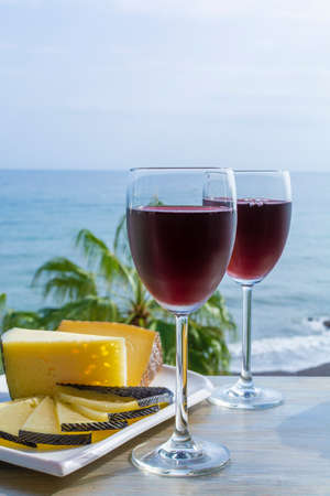 Red wine served in glasses with spanish cheese in outdoor lounge bar with sea view and palm trees