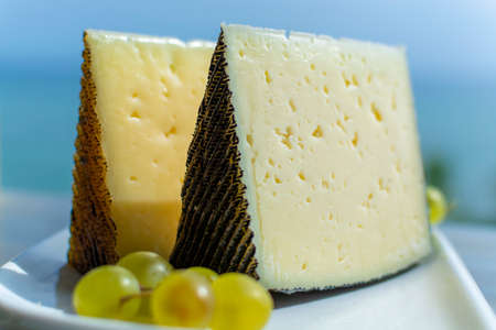 Spanish sheep cheese served with white outside with sea view close up Reklamní fotografie