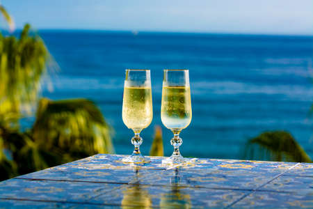 Romantic event, bottle with cold sparkling wine, cava or champagne served with two glasses on table with sea view and tropical palm tree Zdjęcie Seryjne - 130755869