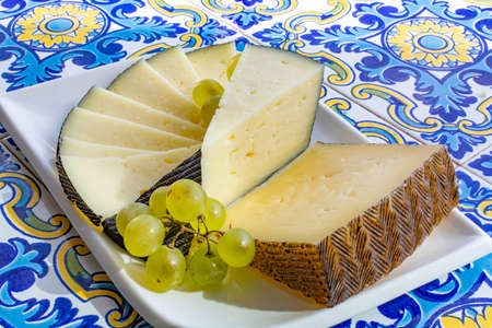 Spanish sheep cheese served with white grapes on andalusian style table Reklamní fotografie - 130755911