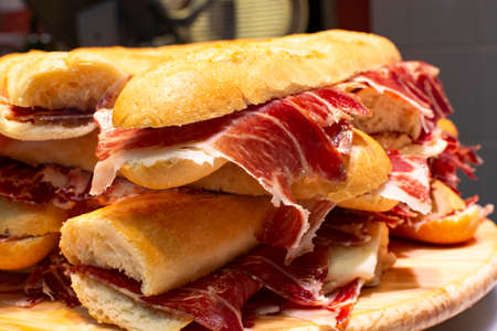 Spanish tapas street food, bocadillo fresh bread with jamon iberico ready to eat