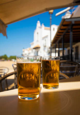 Cold amber color light spanish beer served in glass in outdoor cafe in town on sand, El Rocio in Andalusia, Spain close up Zdjęcie Seryjne - 130755970