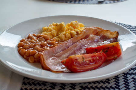 English breakfast with grilled bacon, tomatoes, scrambled eggs and baked beans in tomato sauce served in Spain Zdjęcie Seryjne - 130755969