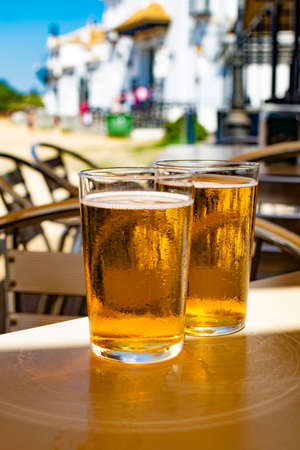 Cold amber color light spanish beer served in glass in outdoor cafe in town on sand, El Rocio in Andalusia, Spain close up Zdjęcie Seryjne