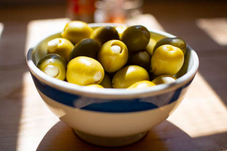 Homemade pickled big green olives stuffed with garlic in bowl, spanish tapas close up Standard-Bild