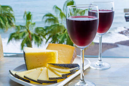Red wine served in glasses with spanish cheese in outdoor lounge bar with sea view and palm trees Zdjęcie Seryjne - 130755981