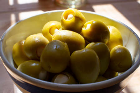 Homemade pickled big green olives stuffed with garlic in bowl, spanish tapas close up Stockfoto