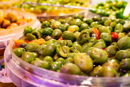 Homemade pickled green olives with garlic and spices in bucket on spanish market