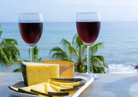 Red wine served in glasses with spanish cheese in outdoor lounge bar with sea view and palm trees Zdjęcie Seryjne - 130756012