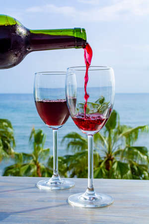 Waiter pouring red wine in glasses in lounge bar with sea view and palm trees close up Zdjęcie Seryjne - 130756016