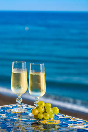 Romantic event, bottle with cold sparkling wine, cava or champagne served with two glasses on table with sea view and tropical palm tree Stock Photo