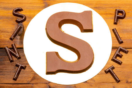 Celebration of Saint Nicholas, patron saint of children in Netherlands, Belgium, Luxembourg and North of France in first week of December, chocolate letters S and names of Sint and Piet close up Stock Photo