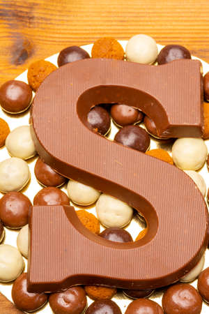 Celebration of Saint Nicholas, patron saint of children in Netherlands, Belgium, Luxembourg and North of France in first week of December, chocolate letters S and ginger cookies close up