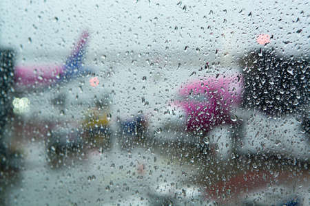 Travel in bad weather conditions concept background with water drops on window with blurred view on colorful airplanes 스톡 콘텐츠