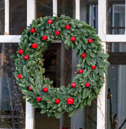 Streen Christmas decoration,big round Christmas wreath made from natural fir decorated with red apples hanging on window close up Standard-Bild - 130756257