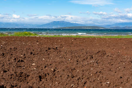 Agriculture in Greece, landscape with plowed field with fertile soil and sea water nearby