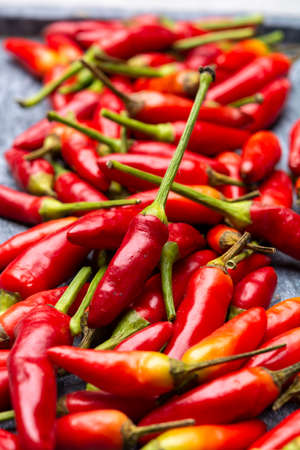 Fresh small red hot chili peppers on grey background close up Stock fotó