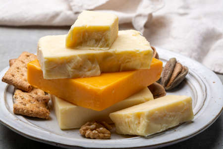 Cheese collection, matured and orange original British cheddar cheese in blocks served with crackers close up Imagens