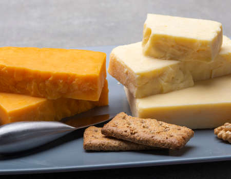 Cheese collection, matured and orange original British cheddar cheese in blocks served on grey plate close up