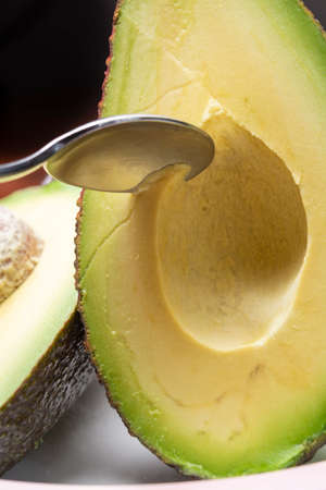 Eating of fresh ripe green organic hass avocado fruit with spoon close up