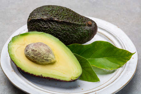 New harvest of fresh ripe hass avocado close cut in half with seed
