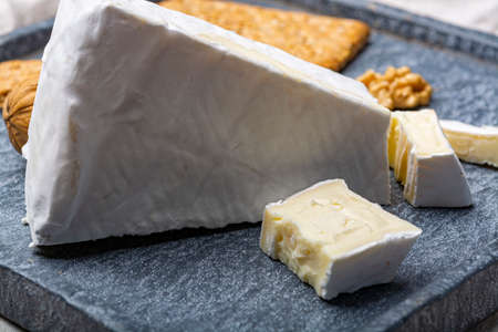 Cheese collection, piece of French brie cheese with white mold close up Stock Photo