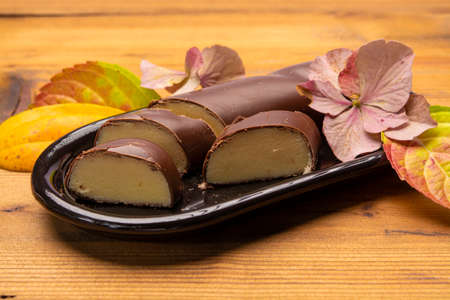 Dutch chocolate candy filled with white marzipan  in autumn colors on dark wooden background close up
