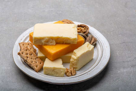 Cheese collection, matured and orange original British cheddar cheese in blocks served with crackers close up Reklamní fotografie