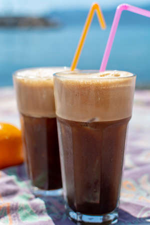 Traditional greek cold coffee Frappe with foam made from water, instant coffee and ice cubes in glass close up