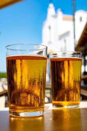 Cold amber color light spanish beer served in glass in outdoor cafe in town on sand, El Rocio in Andalusia, Spain close up Archivio Fotografico