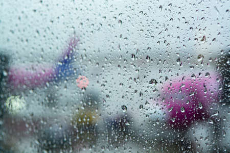 Travel in bad weather conditions concept background with water drops on window with blurred view on colorful airplanes Stok Fotoğraf
