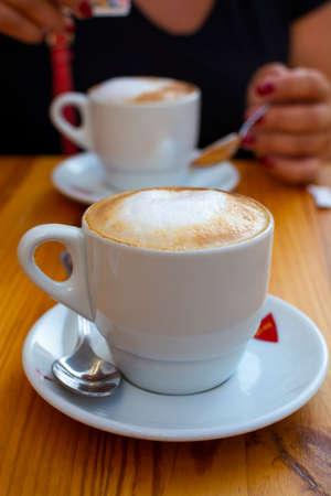 Witte kop met cappuccino-koffie met opgeklopte warme melk die buiten in café wordt geserveerd