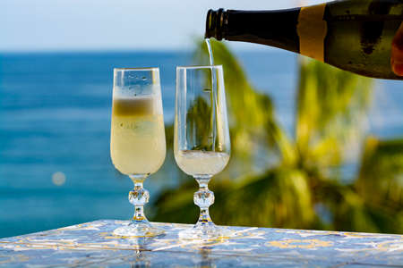 Romantic event, waiter pouring cold sparkling wine, cava or champagne served with two glasses on table with sea view and tropical palm tree Foto de archivo