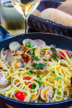 Spaghetti with sea clams, pasta vongole served in cooking pan, tasty italian seafood close up 写真素材