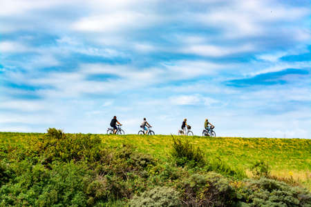 Vier Personen, die an einem sonnigen Tag in den Niederlanden auf Fahrrädern fahren, Sportkonzept