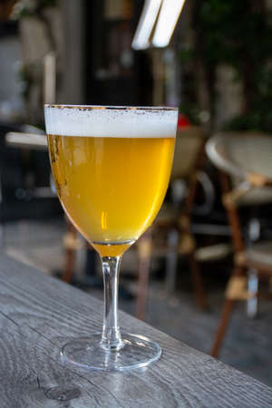 Famous Belgian beer served outside in small old cafe in special Belgian beer glass in sun lights