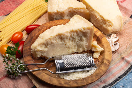 Cooking with hard italian cheese, grated parmesan or grana padano cheese close up Stock Photo
