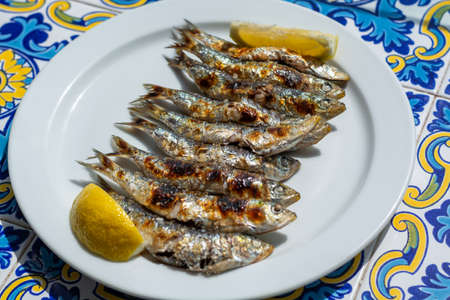 Sardines espeto, Malaga style fish on stick barbecue prepared on olive tree firewoods on beach 写真素材