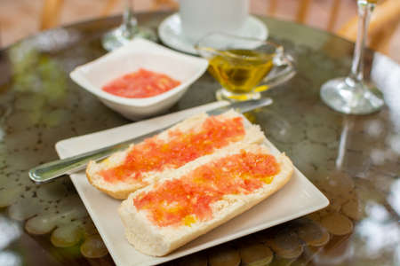 Traditional andalusian breakfast with bread toasts, fresh ground tomatoes sauce and olive oil 版權商用圖片