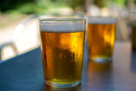 Cold amber color light spanish beer served in glass in outdoor cafe in sunny Andalusia, Spain close up 스톡 콘텐츠