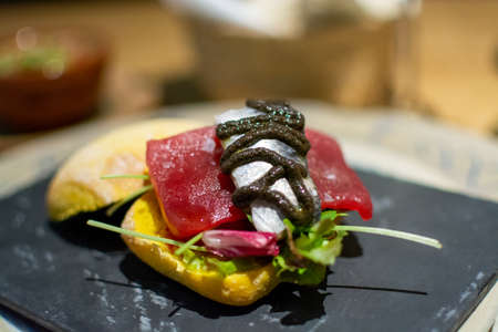 Andalusian gourmet food tapas, small curry bread with blue tuna fish and sardine close up