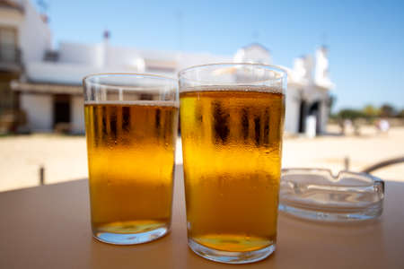 Cold amber color light spanish beer served in glass in outdoor cafe in town on sand, El Rocio in Andalusia, Spain close up 스톡 콘텐츠