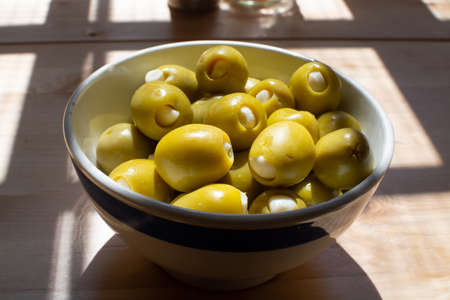 Homemade pickled big green olives stuffed with garlic in bowl, spanish tapas close up Stock Photo