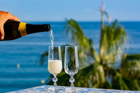 Romantic event, waiter pouring cold sparkling wine, cava or champagne served with two glasses on table with sea view and tropical palm tree