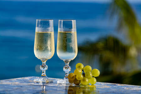 Romantic event, bottle with cold sparkling wine, cava or champagne served with two glasses on table with sea view and tropical palm tree 스톡 콘텐츠