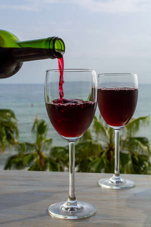 Waiter pouring red wine in glasses in lounge bar with sea view and palm trees close up
