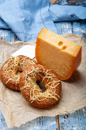 Tasty baked bagels with melted cheese and piece of aged Dutch Gouda cheese close up Фото со стока