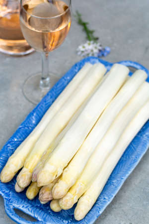 Fresh raw washed and peeled white asparagus vegetables ready to cook and rose wine