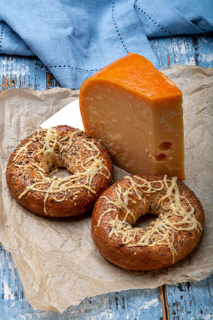 Tasty baked bagels with melted cheese and piece of aged Dutch Gouda cheese close up 写真素材